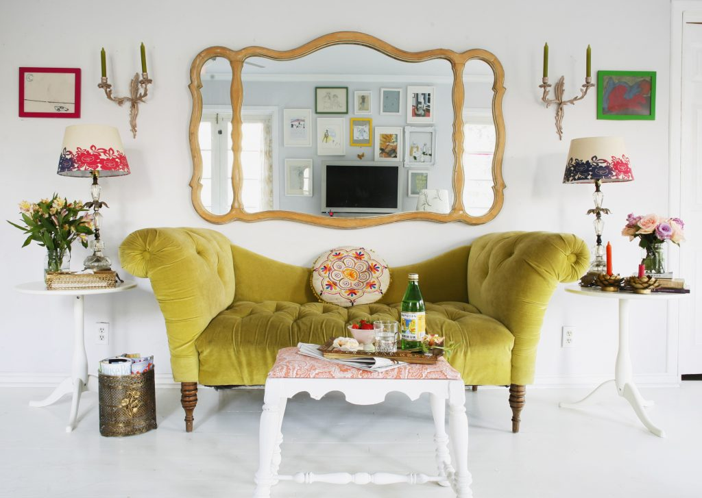Bright green velvet sofa in an all white room with colourful, eclectic furnishings and accessories.